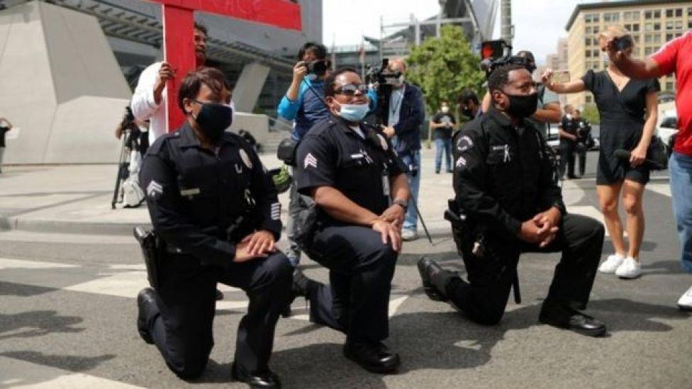 Policías arrodillados en una protesta