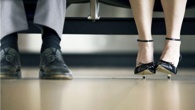 A man's feet next to a woman's feet