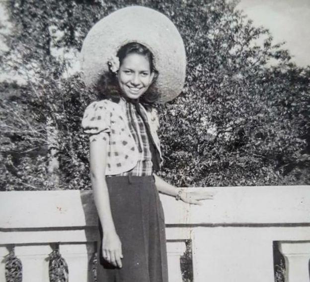 Grace portant un énorme chapeau devant un pont