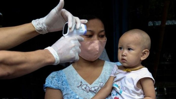 Un jeune enfant se fait prendre sa température par un professionnel de la santé