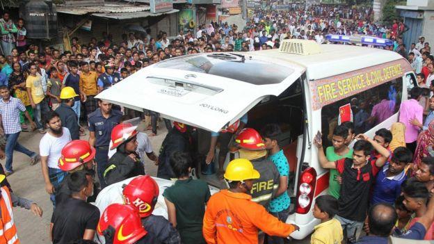 Feuerwehrleute tragen Opfer zu einem Krankenwagen nach Fabrik Feuer in Tongi, Bangladesch, am 10. September 2016