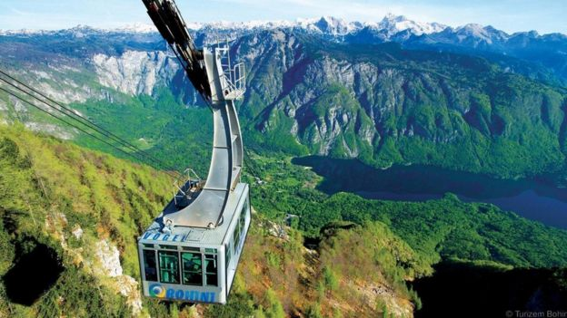 A cable car pulls up to the snow-covered top of Mount Vogel