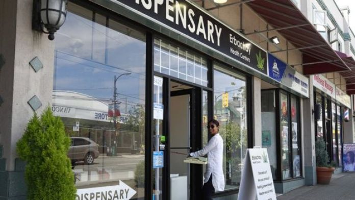 A woman walks into the Erbachay Health Centre Dispensary in Vancouver