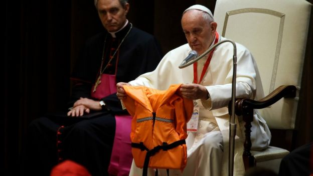 Pope Francis holds a life jacket which was donated to him by a migrants