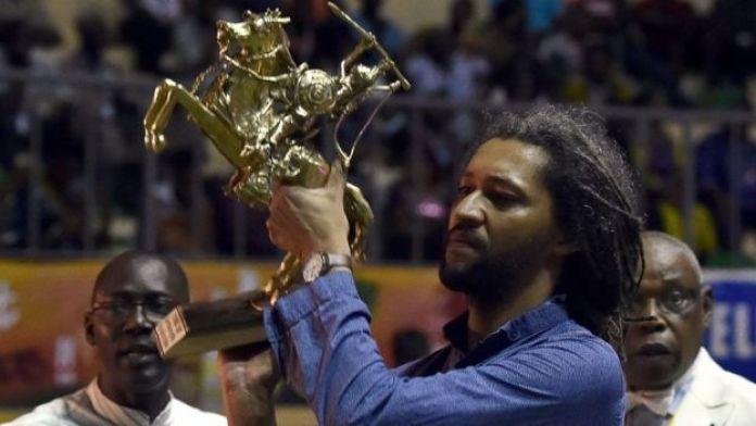 Le réalisateur franco-sénégalais Alain Gomis soulève l'Étalon de Yennenga, le Grand Prix du Fespaco qu'il a remporté en 2013 et 2017.