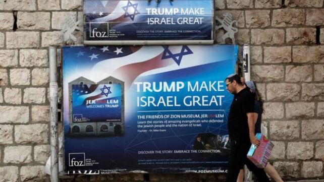 Israelis walk past a poster welcoming and supporting US President Donald Trump in Jerusalem, on May 19, 2017