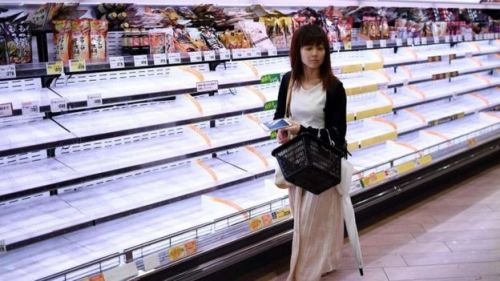 A woman walks past empty shelves in a store in Tokyo