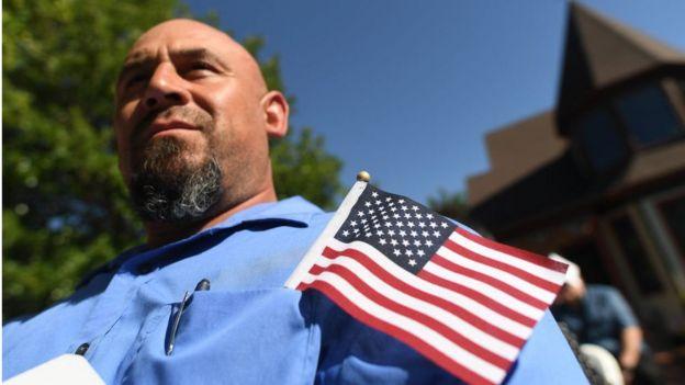 Un hombre con una bandera estadounidense en su bolsillo durante una ceremonia de naturalización