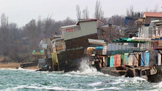 Casas sendo derrubadas por ondas