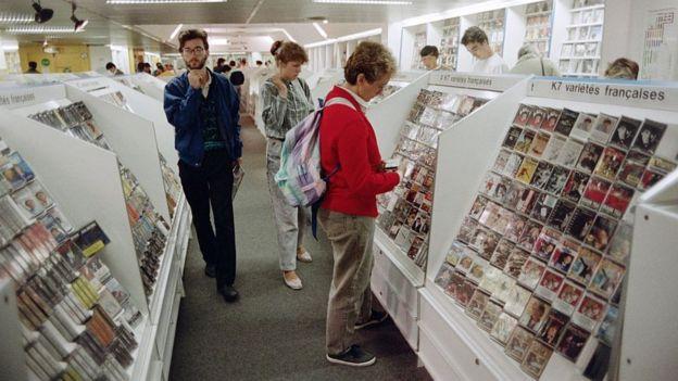 ينظر العملاء إلى أشرطة الموسيقى المعروضة في أحد المتاجر في باريس في 28 أغسطس 1987