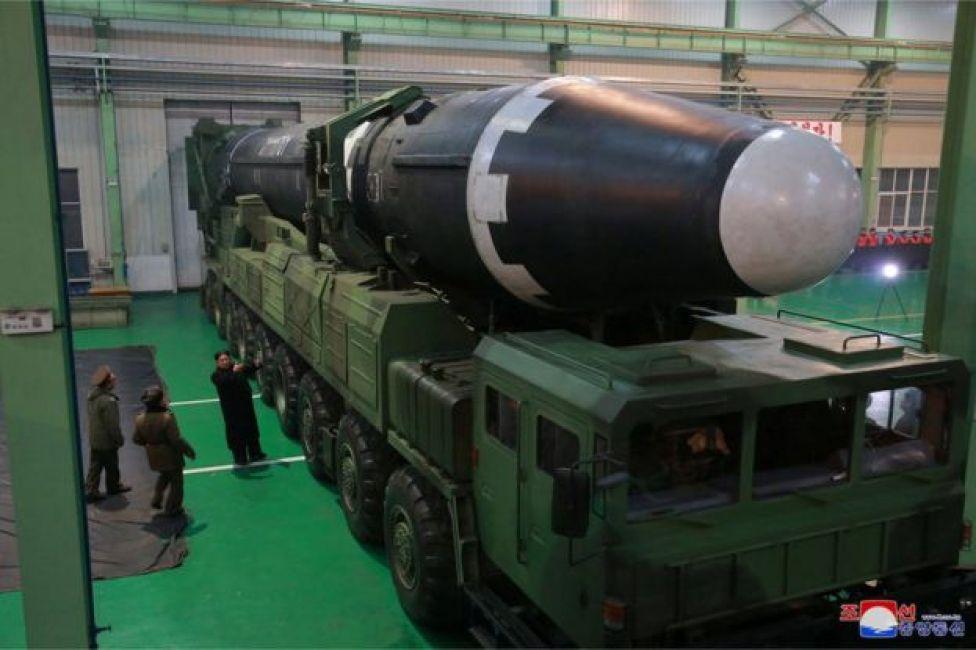 El líder norcoreano, Kim Jong-un de pie al lado del vehículo que transporta el misil.