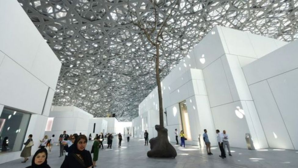 People walk near a sculpture by Italian artist Giuseppe Penone at the Louvre Abu Dhabi Museum on 7 November 2017, on the eve of the official opening of the museum on Saadiyat island in the Emirati capital.