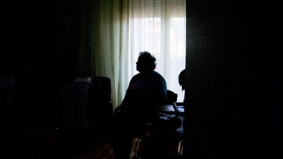 Mujer mayor sentada sola