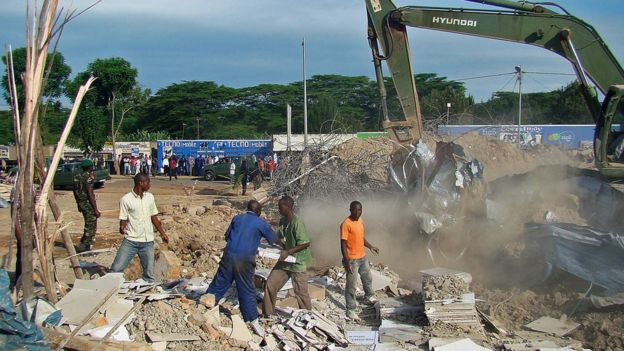 Earthmoving equipment removes debris from a collapsed building in Nyagatare, north eastern Rwanda on May 15, 2013. The collapse killed 6 people and injured dozens. Both police and the army worked to free those trapped in the rubble, with at least 30 people pulled from the debris alive. AFP PHOTO /Stephanie Aglietti