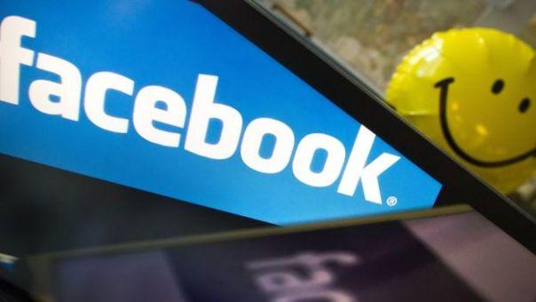Un logotipo de Facebook proyectado en una pantalla y, al fondo, un emoji sonriente.