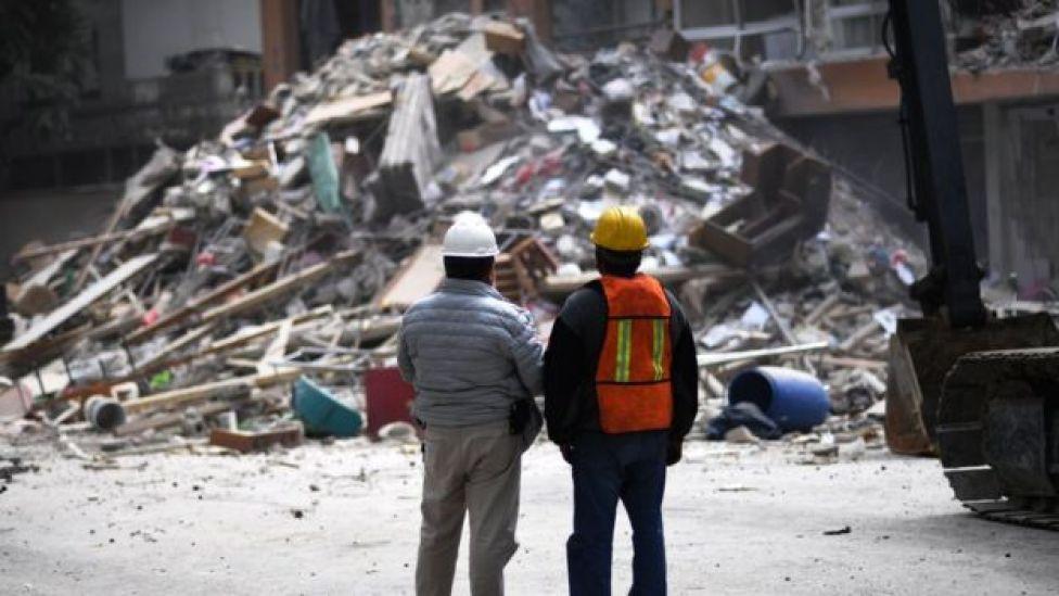 Dos hombres de espaldas miran una pila de escombros en México en septiembre de 2017