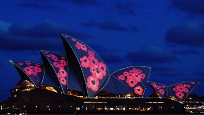 The sails of the Sydney Opera House are seen illuminated with red poppies