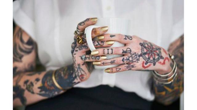 Mulher com braços e mãos tatuadas