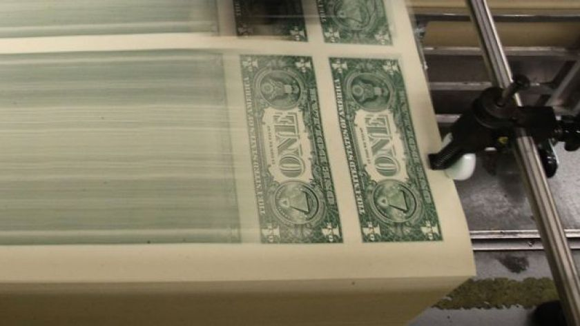 Dollar bills roll off a US government printing press.