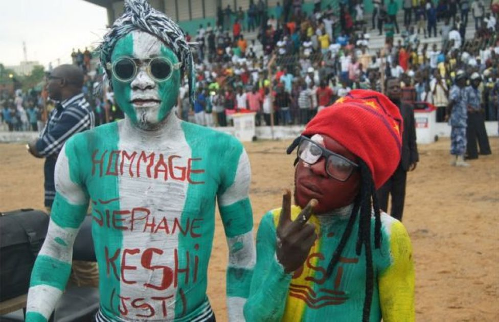 Man covered in bodypaint in Nigeria's green and white colours, with the message hommage to Stephen Keshi, stands in stadium 20 June 2016