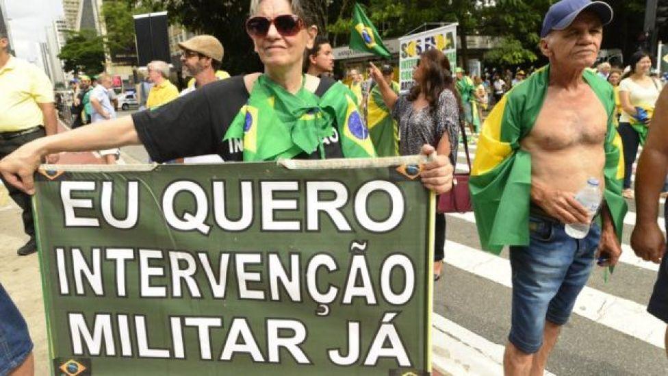 Mujer con cartel que pide intervención militar en Brasil