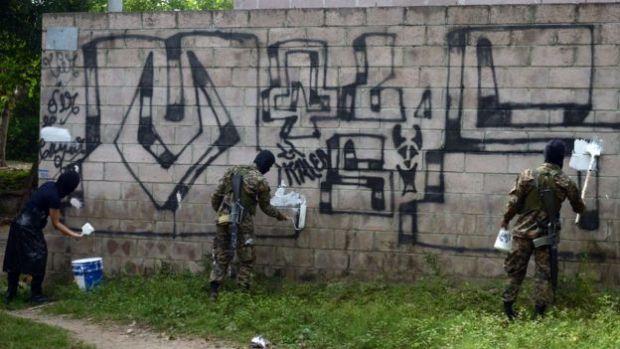 Policías borrando pintas alusivas a la Mara Salvatrucha en una pared de ladrillo de Quezaltepeque, una ciudad a 15 kilómetros de San Salvador.