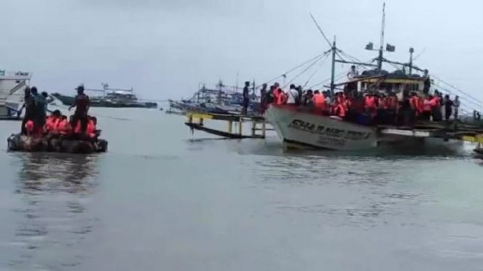 Passengers of a capsized ferry are brought ashore off the coast of the Philippines