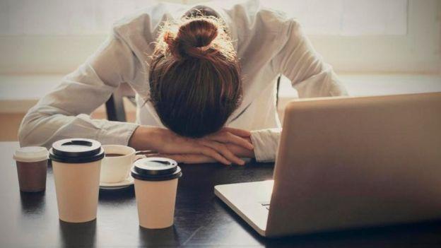 Una mujer agobiada que se recuesta sobre su escritorio
