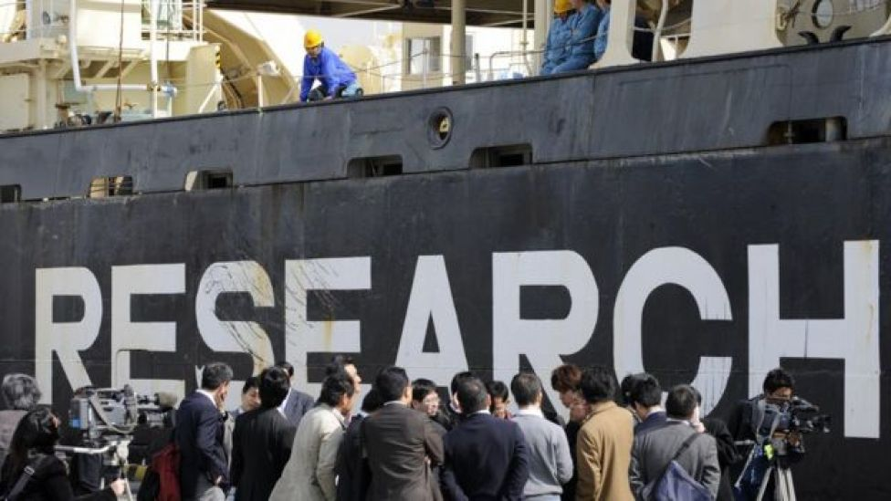 Journalists next to a Japanese whaling ship branded with the word Research (in 1980)