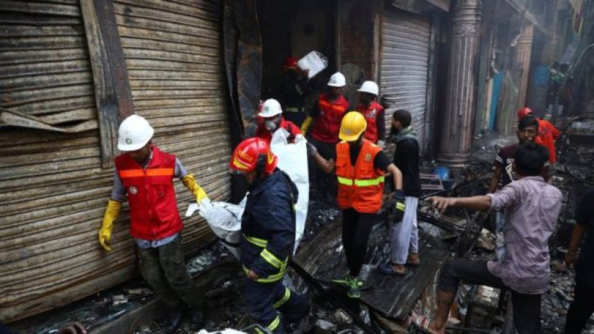 Volunteers recover a dead body from a burnt warehouse in Dhaka