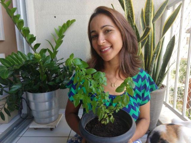 A relações públicas Renata Ribeiro segurando um vaso com um pé de manjericão