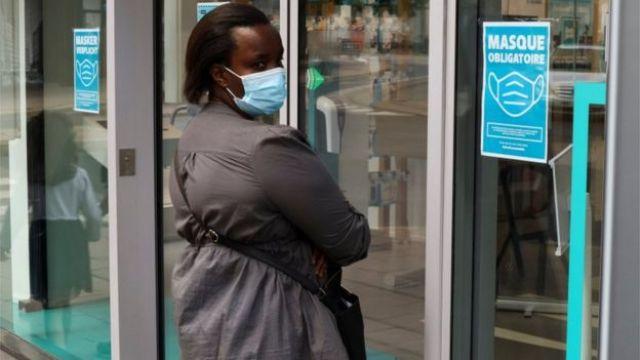Une femme portant un masque à Anvers entre dans une boutique