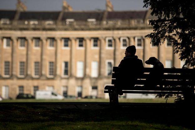 Bir adam ve köpeği bankta oturuyor