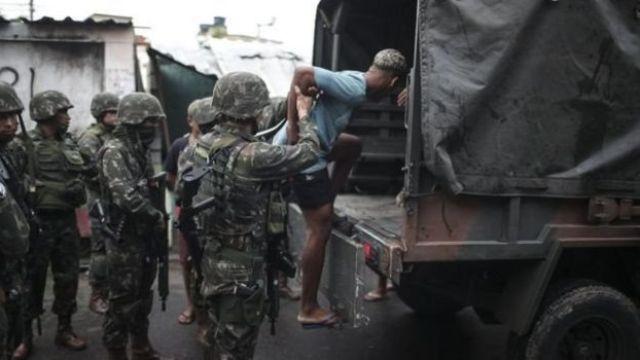 Homem é colocado em caminhão do Exército