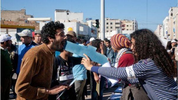 Protesta en Marruecos. Mujer sostiene logo de Facebook