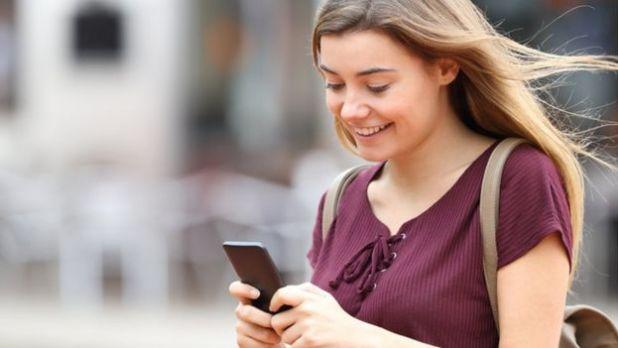 Una joven escribe en un teléfono.