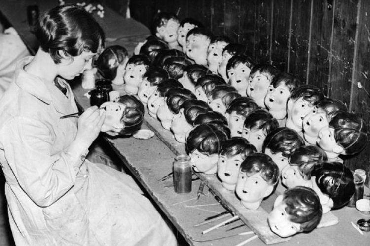 Un operaio che dipinge le bambole di celluloide testa in una fabbrica a Leicester nel 1935
