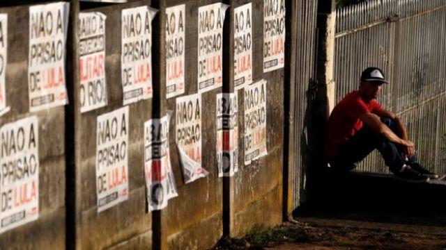 Homem ao lado de cartazes com os dizeres 'Não à prisão de Lula'