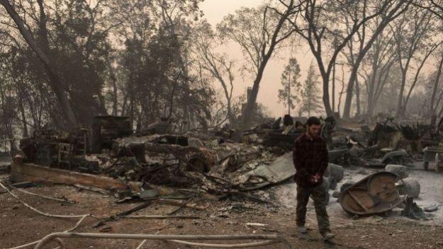 Un joven camina por los restos de su casa, ahora en cenizas