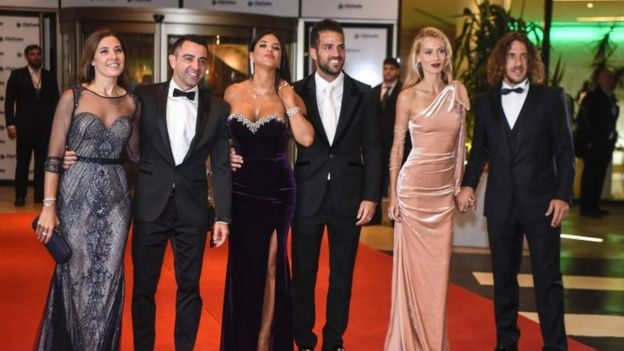 Former Barcelona players Xavi Hernandez, Cesc Fabregas and Carles Puyol and their wives pose on a red carpet upon arrival to attend Argentine football star Lionel Messi and Antonella Roccuzzo