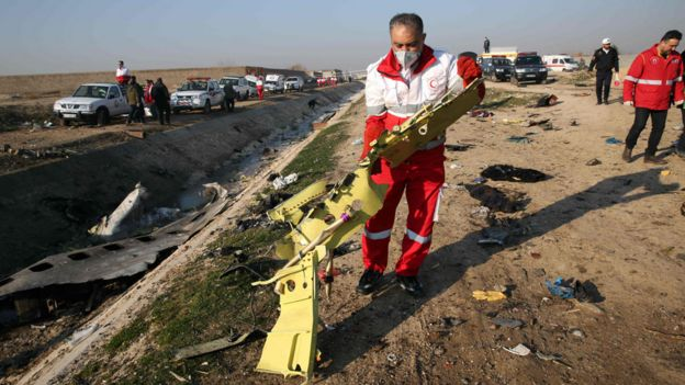 Red Crescent workers check the debris from the Ukraine International Airlines plane