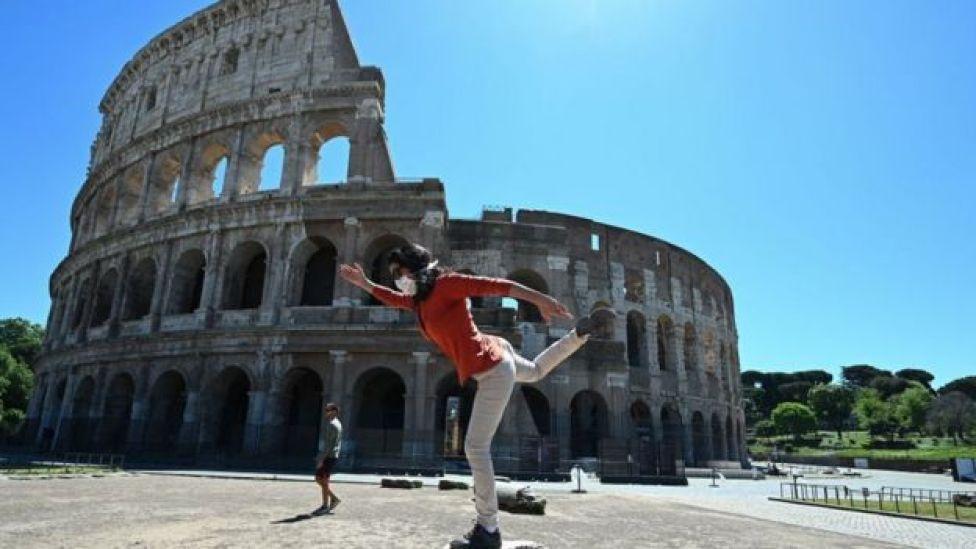 Mulher fazendo exercícios em frente ao Coliseu de Roma