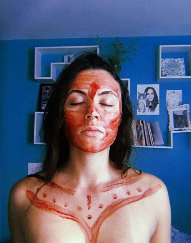 Laura, médica de 27 anos com o rosto e parte do colo coberto com sangue de menstruação