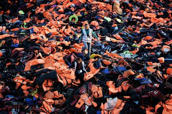 Volunteers walk on a huge pile of lifejackets left behind by refugees and migrants who arrived to the Greek island of Lesbos after crossing the Aegean sea from Turkey on December 3, 2015.