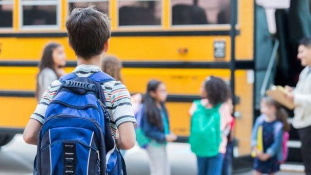 Criança caminha para o ônibus escolas