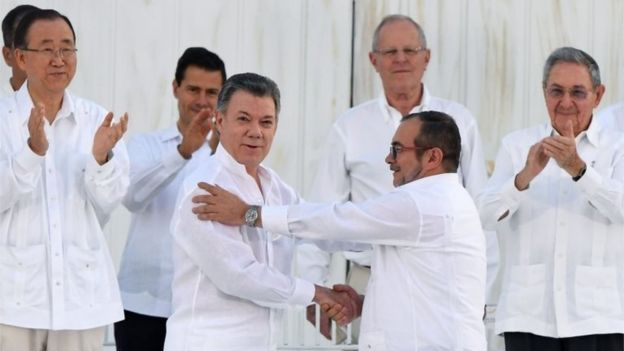 This file photo taken on September 26, 2016 shows Colombian President Juan Manuel Santos (L at centre) and the head of the FARC guerrilla Timoleon Jimenez, aka Timochenko, during the signing of the historic peace agreement between the Colombian government and the Revolutionary Armed Forces of Colombia (FARC), in Cartagena.