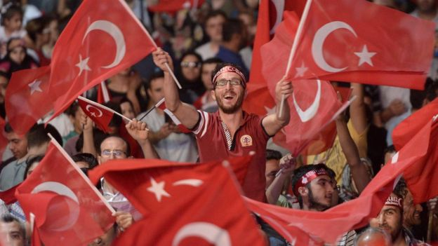Bir gösterici ellerinde Türk bayrakları sallıyor.