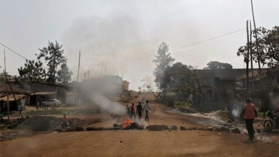 People walk by a burning tyres, on December 27, 2018 in Beni