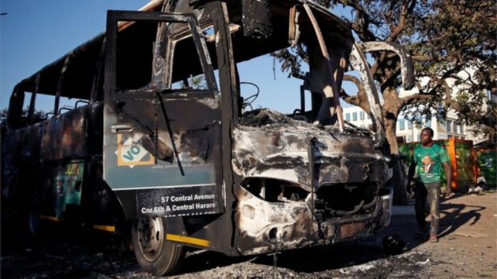 """A supporter of the ruling ZANU-PF walks past a burnt vehicle at the party""""s offices a day after the clashes between security forces and opposition protesters in Harare, Zimbabwe, August 2, 2018"""
