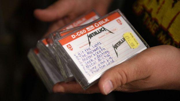 موظف في متجر للموسيقى يحمل نسخًا من الشريط التوضيحي الذي أعيد إصداره من شركة Metallica عام 1982